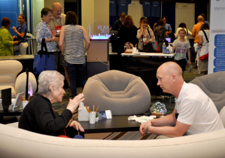 Photo from Convention 2016 Exhibit Hall, two people talking