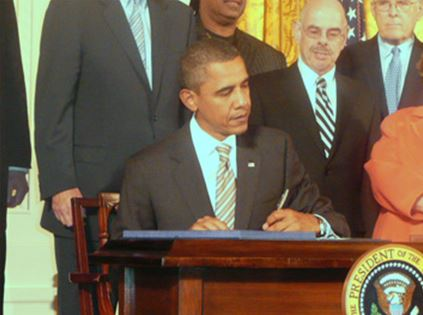 President Obama signing CVAA into law and surrounded by others.