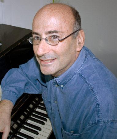 Richard Einhorn sitting by a piano