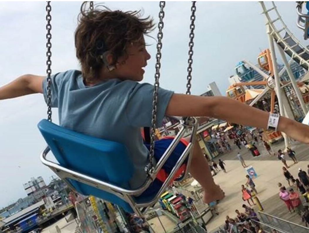 Young boy in swing at amusement park